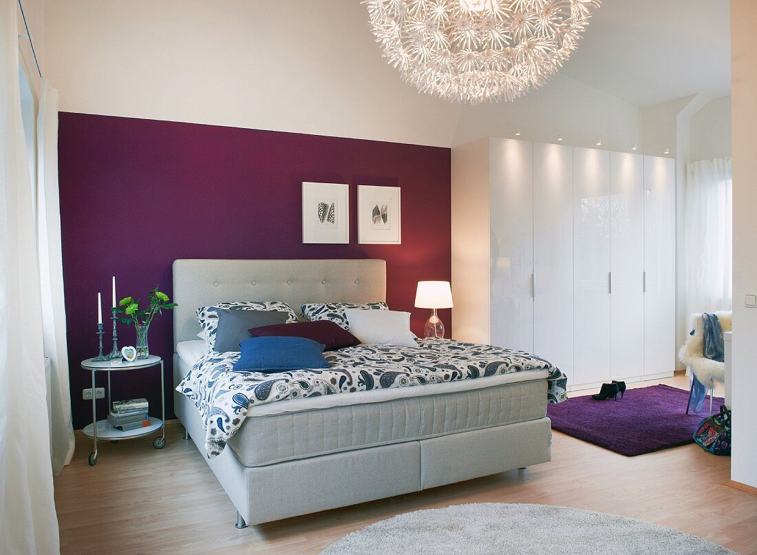 A bedroom with a light grey boxspring bed against a purple wall with a white, multi-door wardrobe to the side