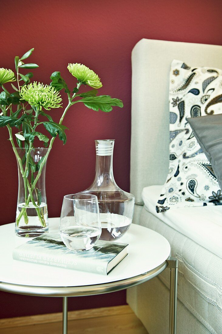 A carafe of water with a drinking glass and a bunch of flowers on a bedside table against a purple wall