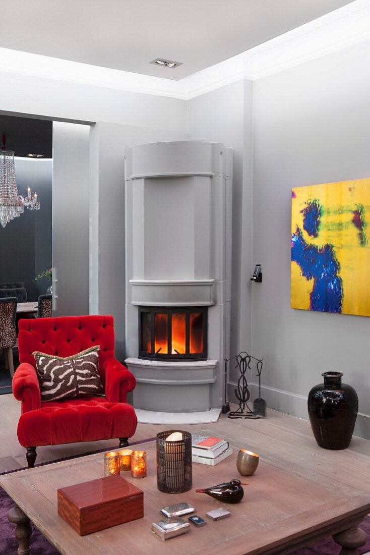 Low, wooden coffee table in front of armchair with red velvet chair and fire in corner fireplace