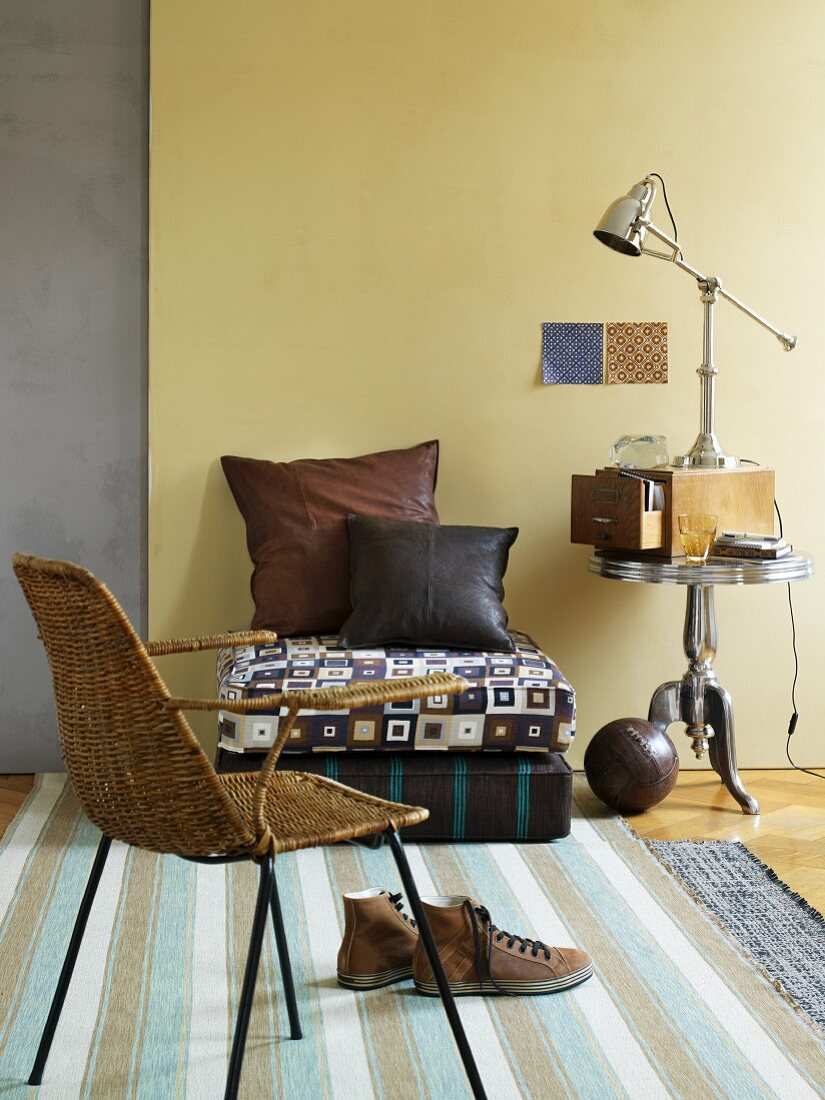 Korbstuhl, Bodenkissen auf Sitzkissen und Leuchte auf Retro Beistelltisch