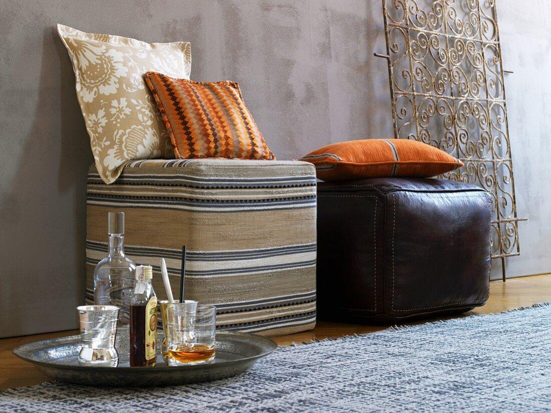 Kissen auf Sitzwürfeln aus gestreiftem Afrikastoff und Leder, dahinter ein Ziergitter