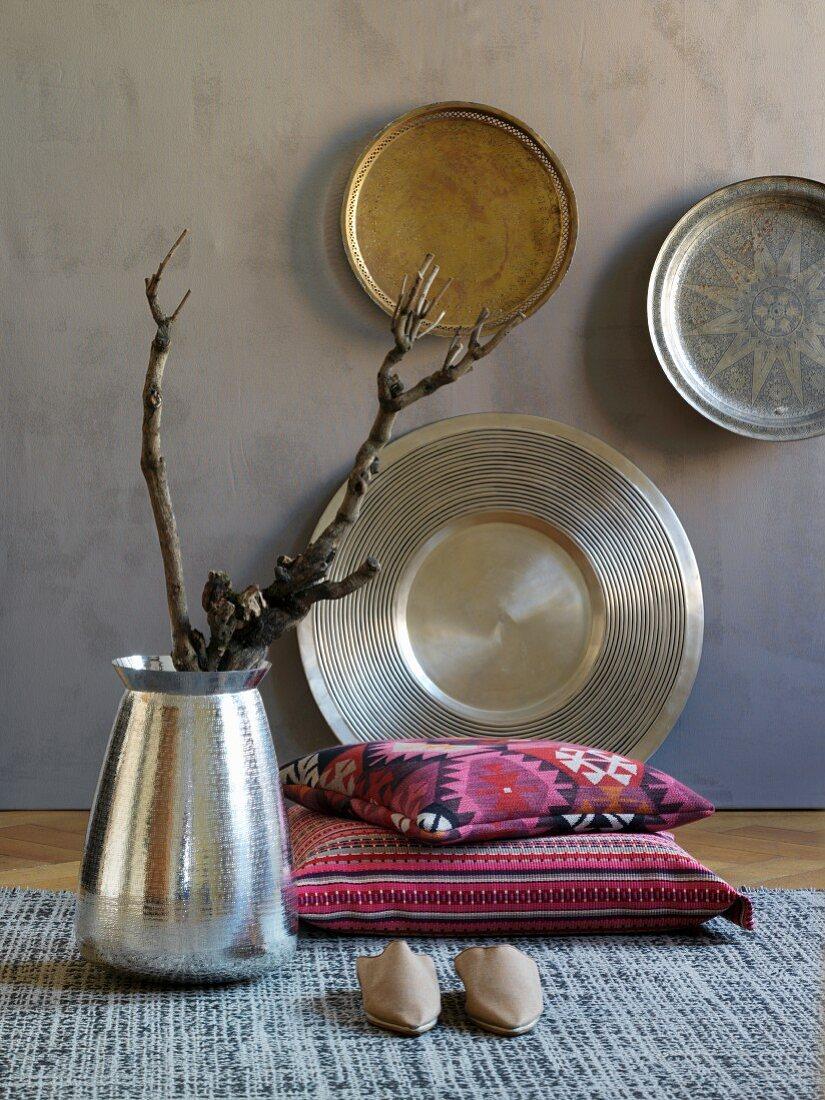 Kunsthandwerkliche Wandteller, Silbervase mit exotischen, groben Zweigen und Kissen mit Folkloremuster