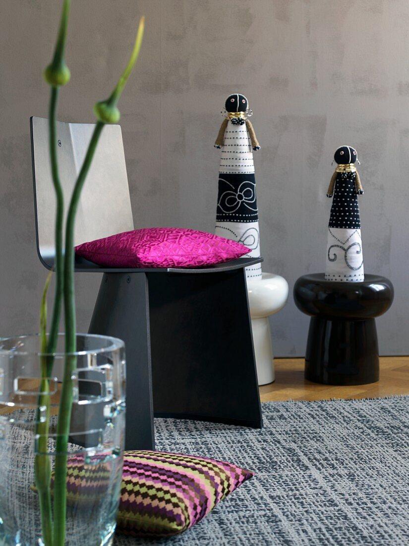 Handgenähte afrikanische Puppen, Stuhl mit pinkfarbenem Kissen, exotische Knospe im Vordergrund