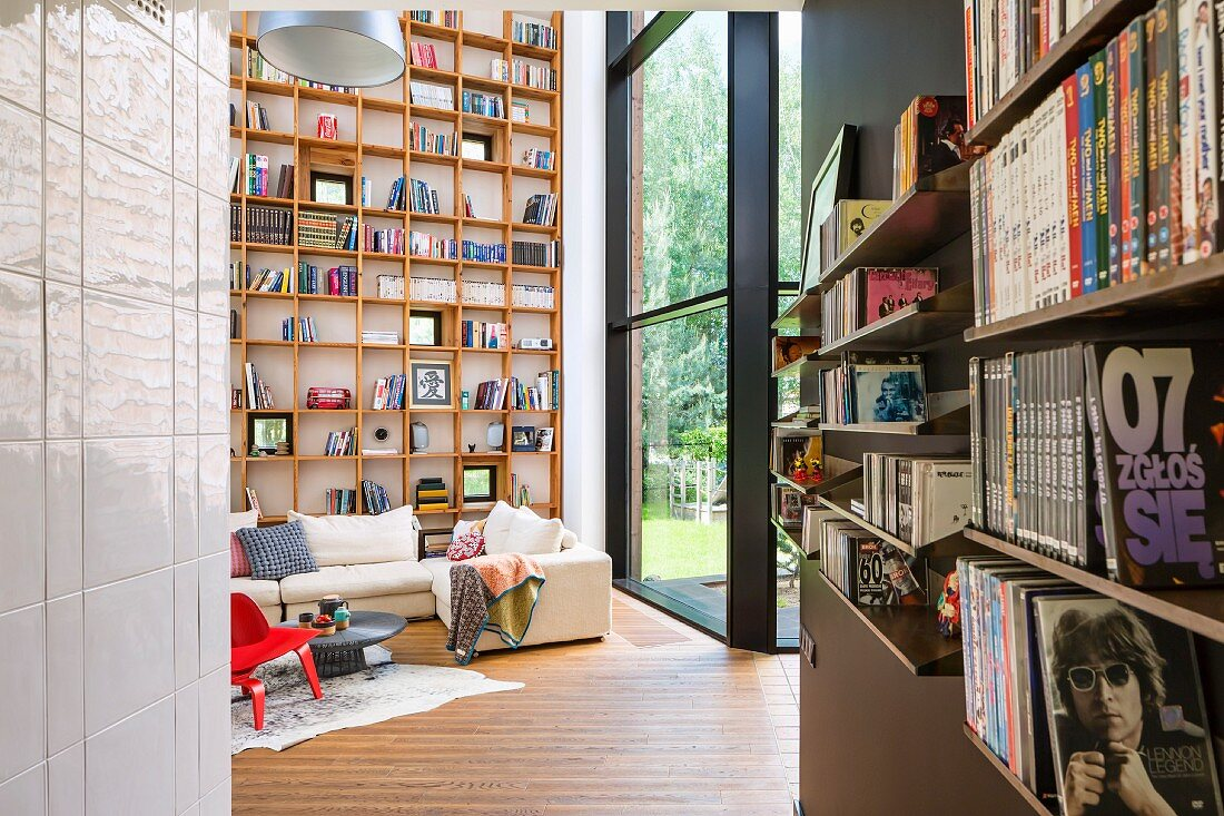 Bookshelves, lounge area with pale sofa and double-height, wooden bookcase in contemporary house