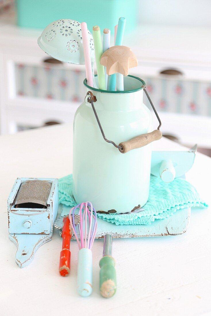 Nostalgic still-life arrangement of pastel kitchen utensils in vintage milk can