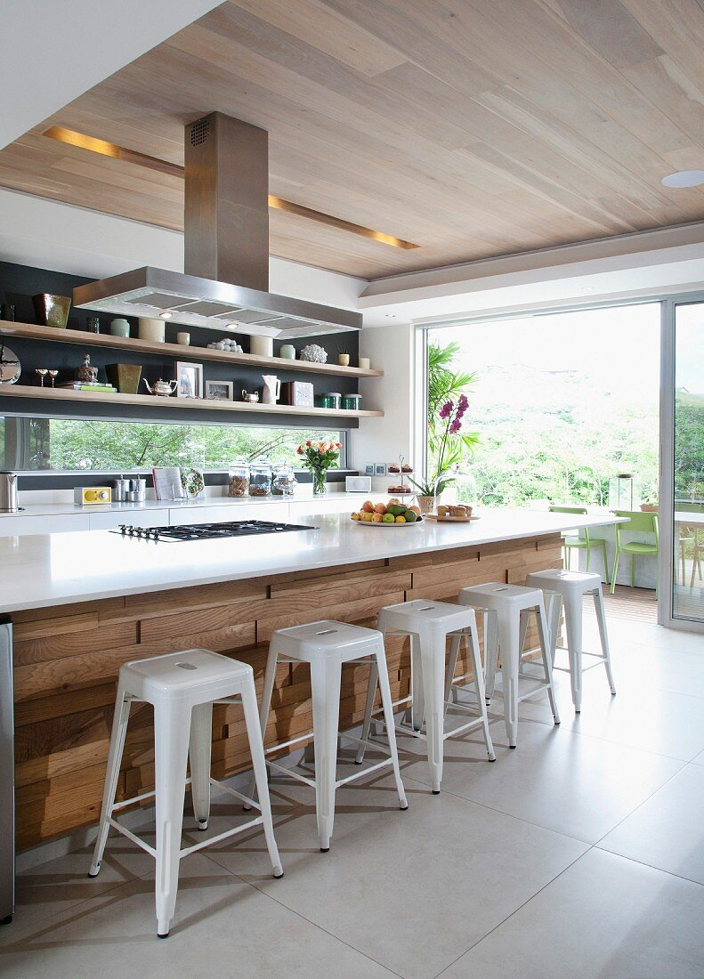 Large island counter with quartz worksurface and oak panelling in designer kitchen