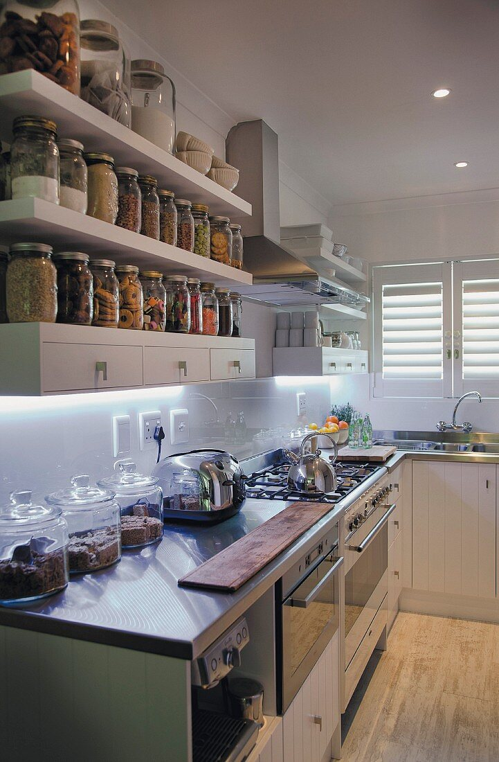 White, fitted kitchen; storage jars on shelves with drawers above kitchen counter