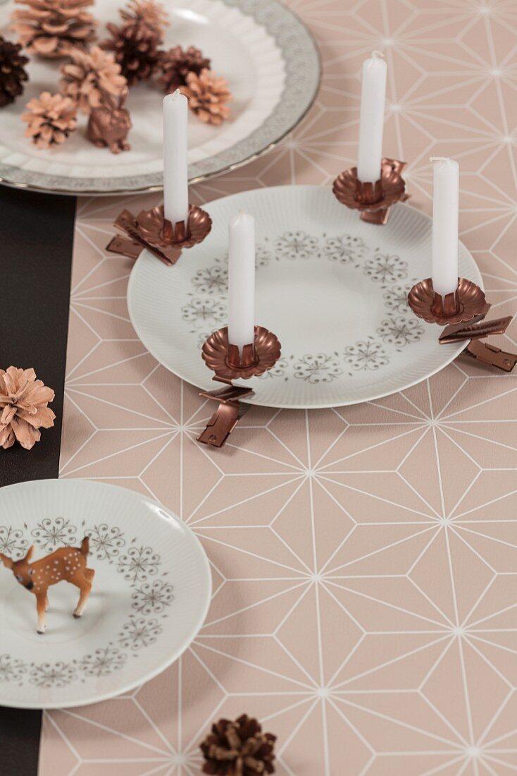Advent arrangement of copper candle clips on porcelain plate