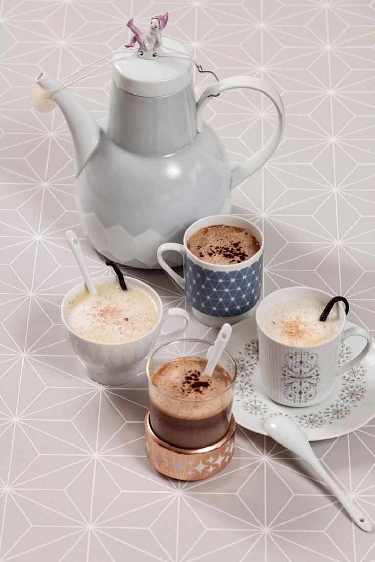 Various cups of wintery hot drinks and coffee pot