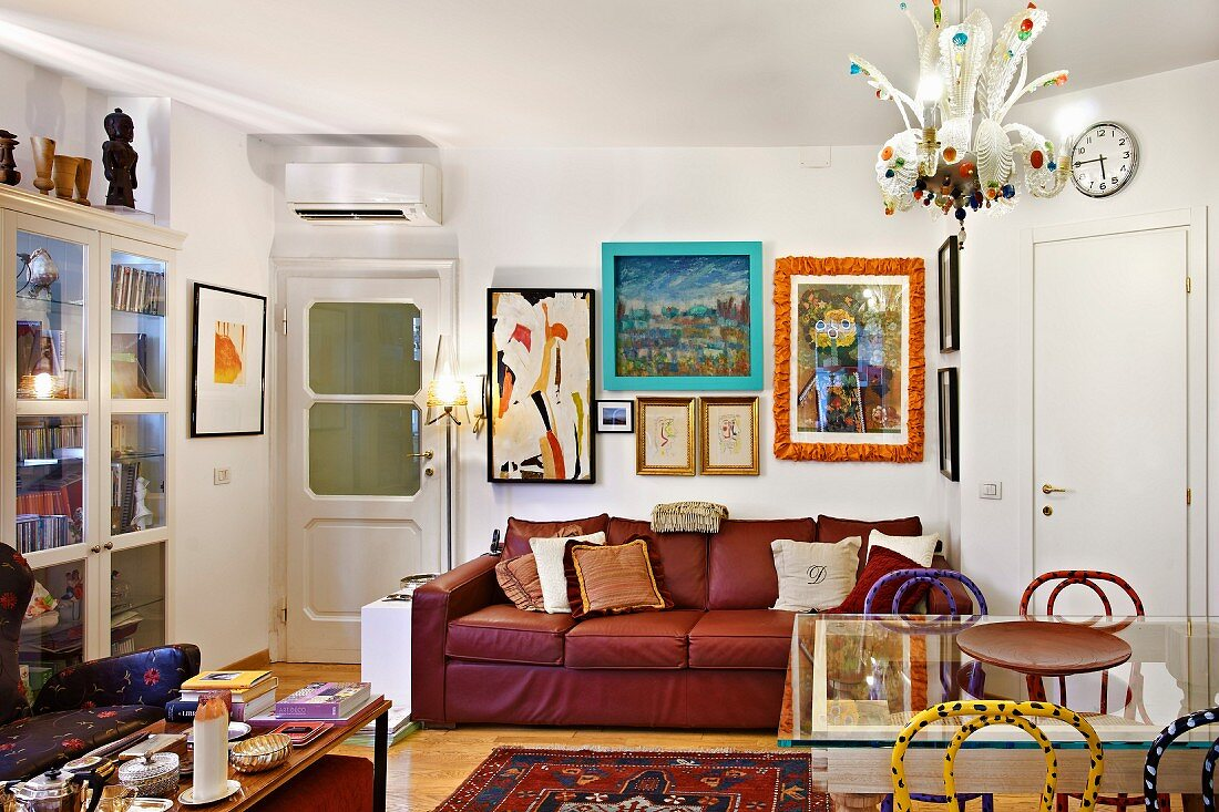 Colourful living room in artist's apartment with comfortable, red leather sofa, various pictures and frames