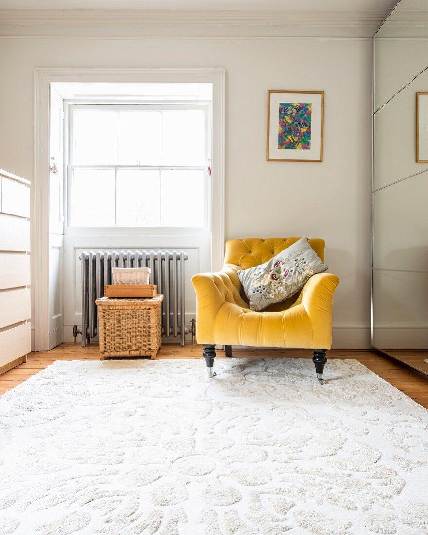 Golden-yellow armchair on white rug next to deep-set window