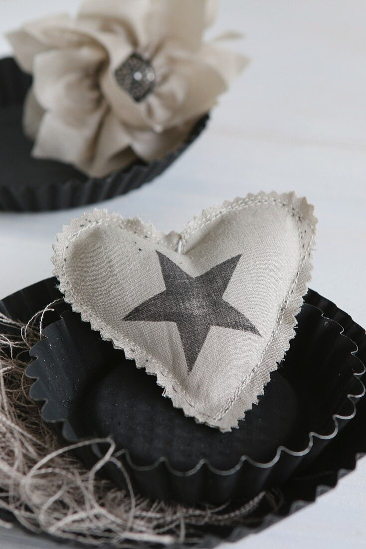 Hand-sewn heart-shaped cushion with star printed on fabric arranged in black cake tin