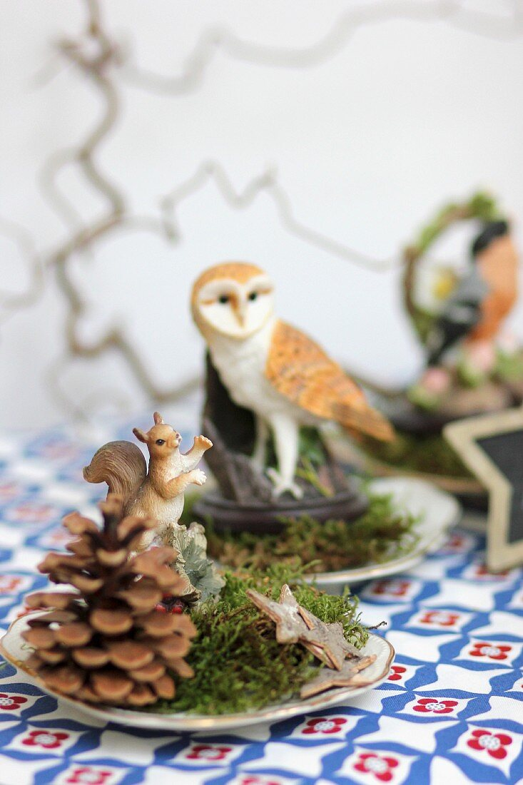 Festive table decorations with pine cones, moss, stars and animal ornaments