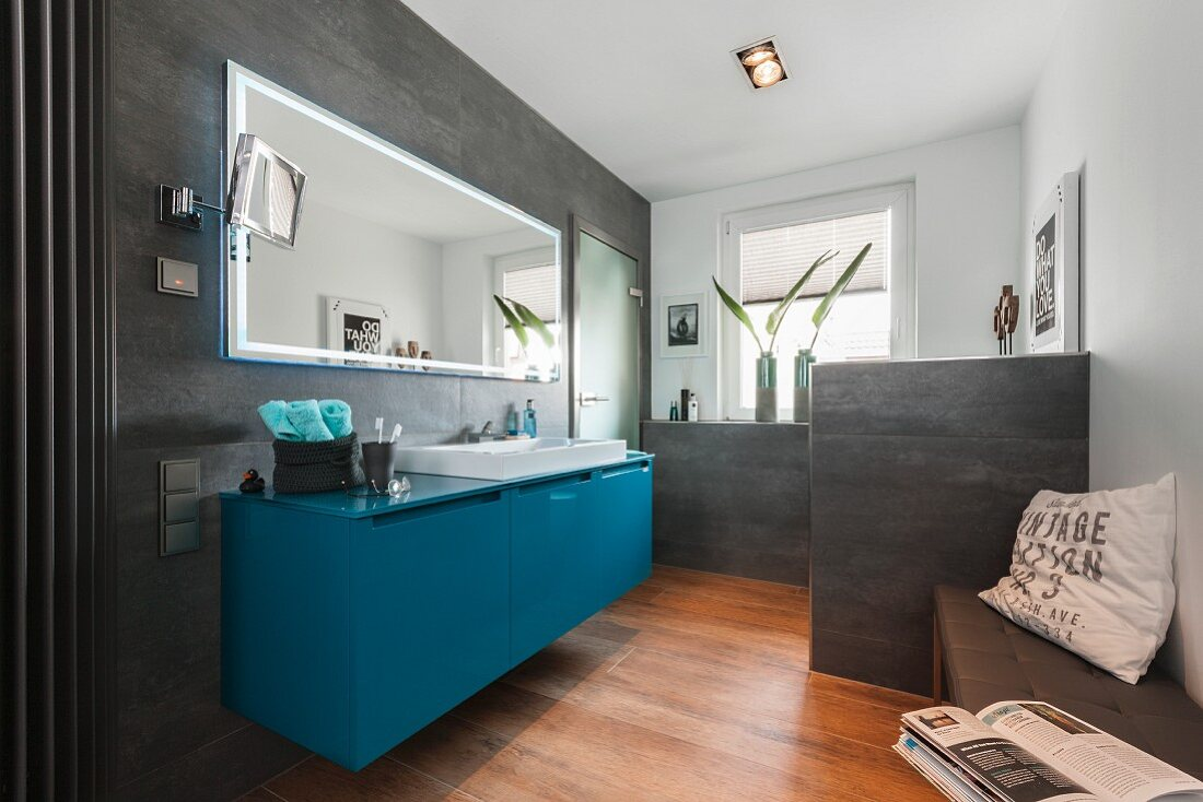 A contemporary bathroom with a petrol-coloured washstand under a mirror with grey tiles on a wall and a partition wall