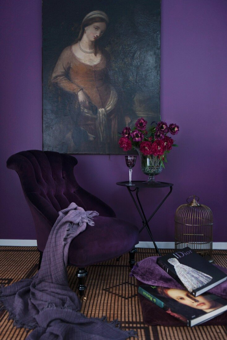 Armchair with purple covers and vase of red flowers on table below oil painting on aubergine wall