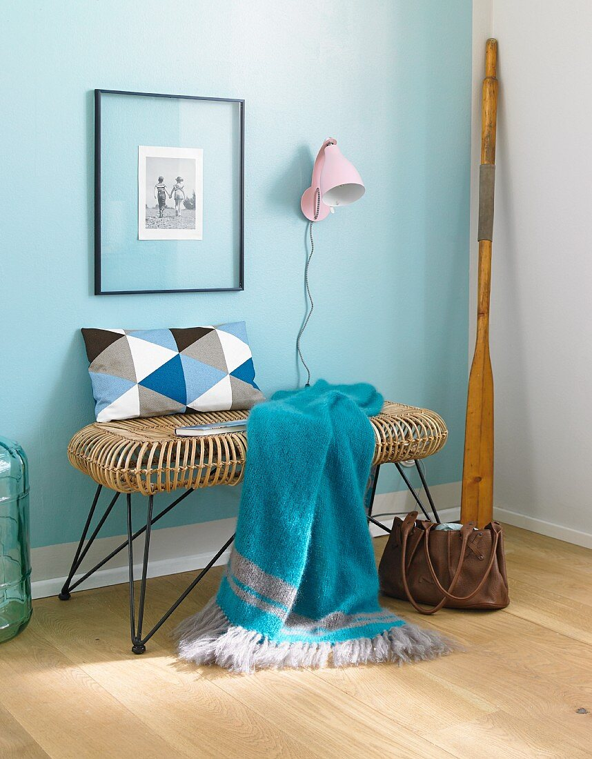 A blue knitted plaid on a 1950s style bench against a pastel-blue wall