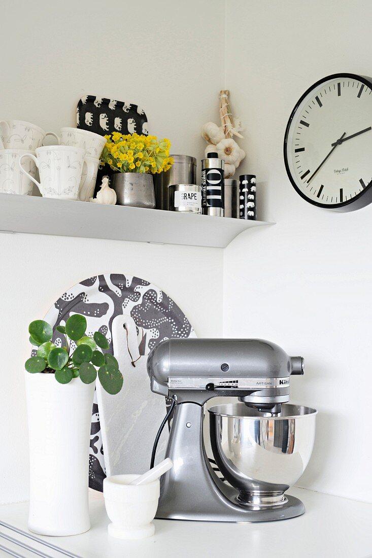 Silver mixer below clock and shelf of cups