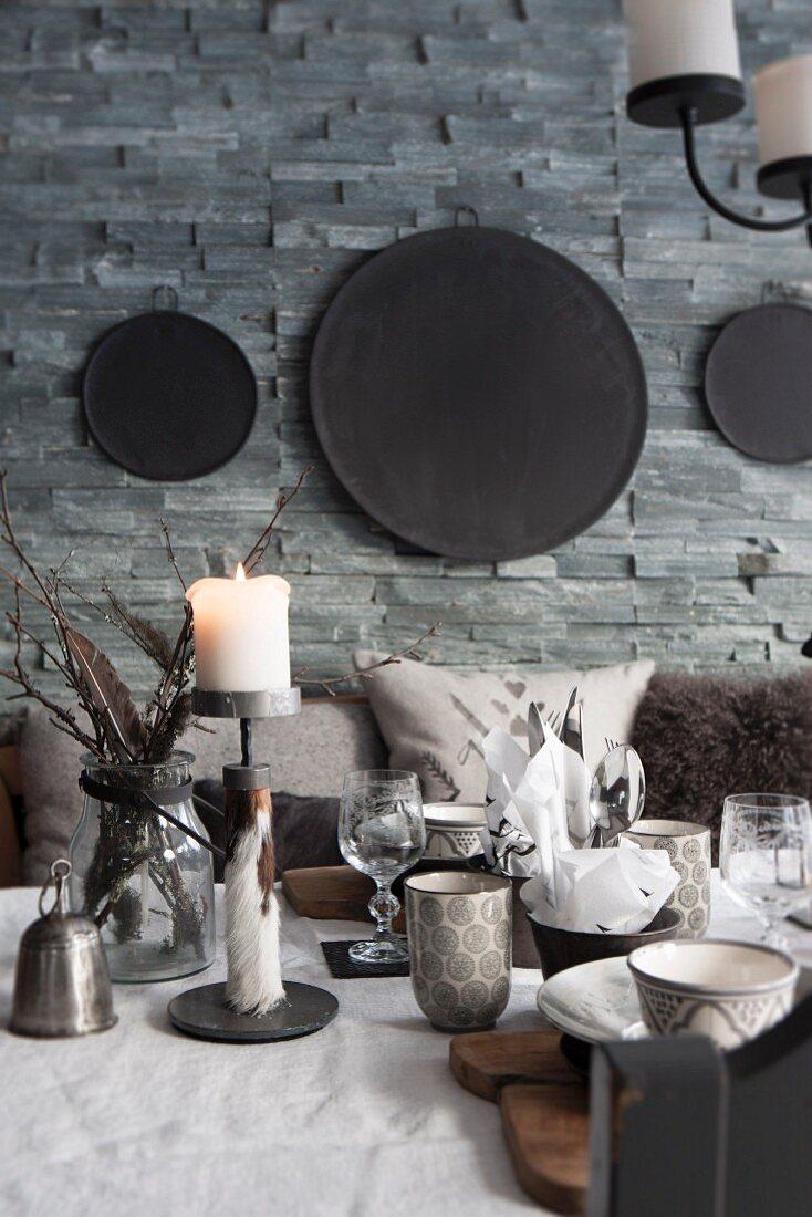 Blick, über gedeckten Tisch mit brennender Kerze, auf Natursteinwand, daran aufgehängte schwarze Metallplatten in verschiedenen Grössen