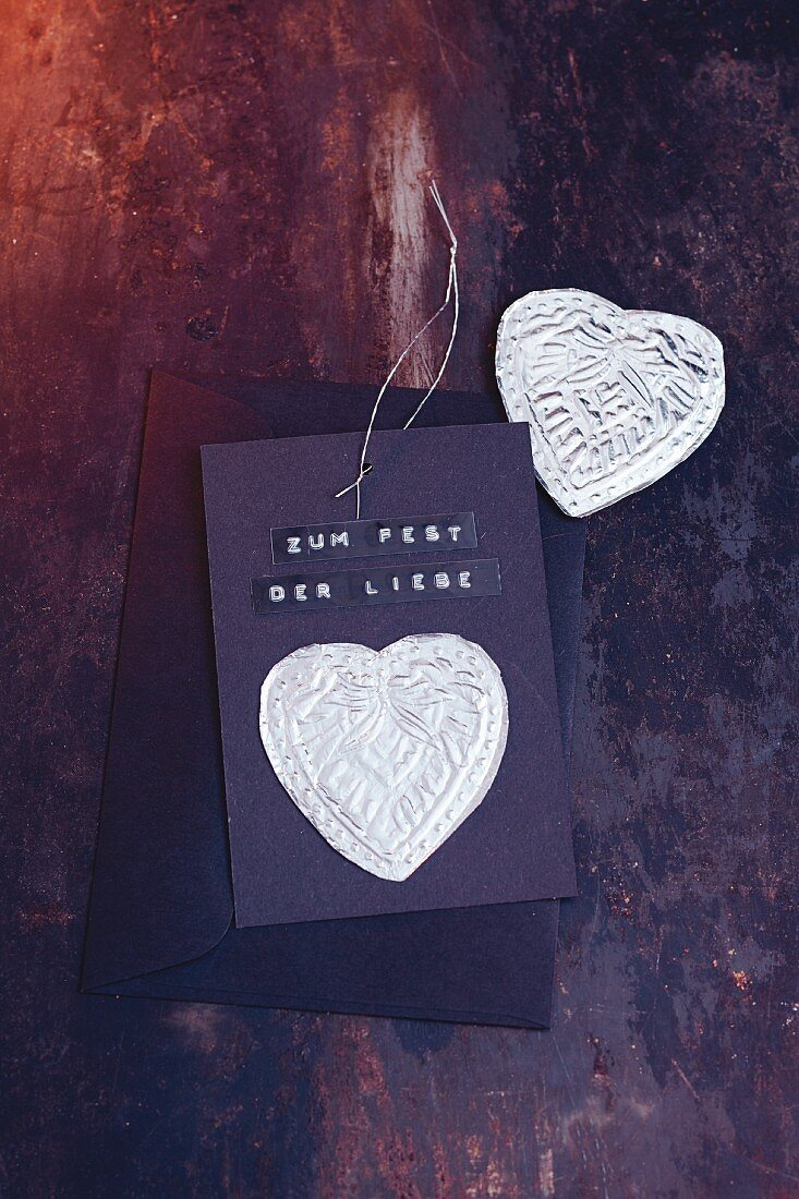 A homemade Christmas card decorated with silver hearts