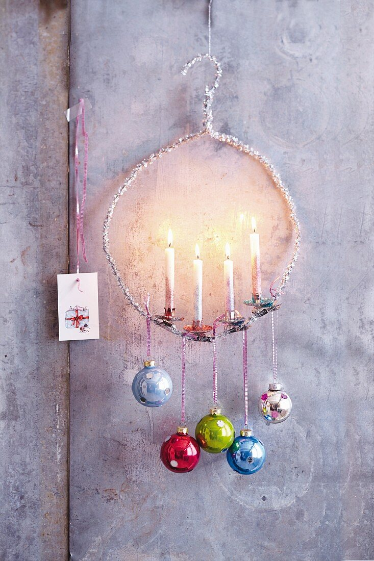 A hanger candle holder decorated with colourful Christmas baubles
