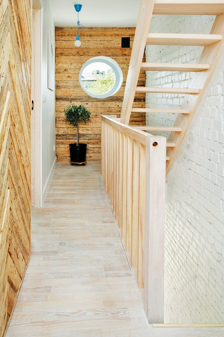 Pale wooden staircase and rustic wood-clad walls in renovated period building with bulls-eye window