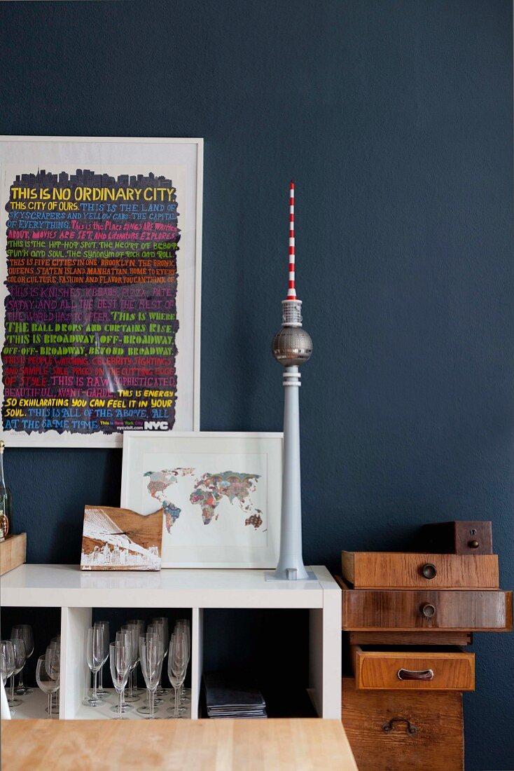 Framed artwork and objets d'art next to stacked vintage wooden drawers