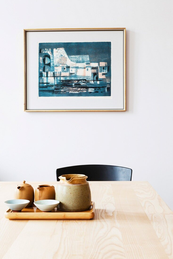 Still-life arrangement of tray and ceramics on wooden table in front of framed picture