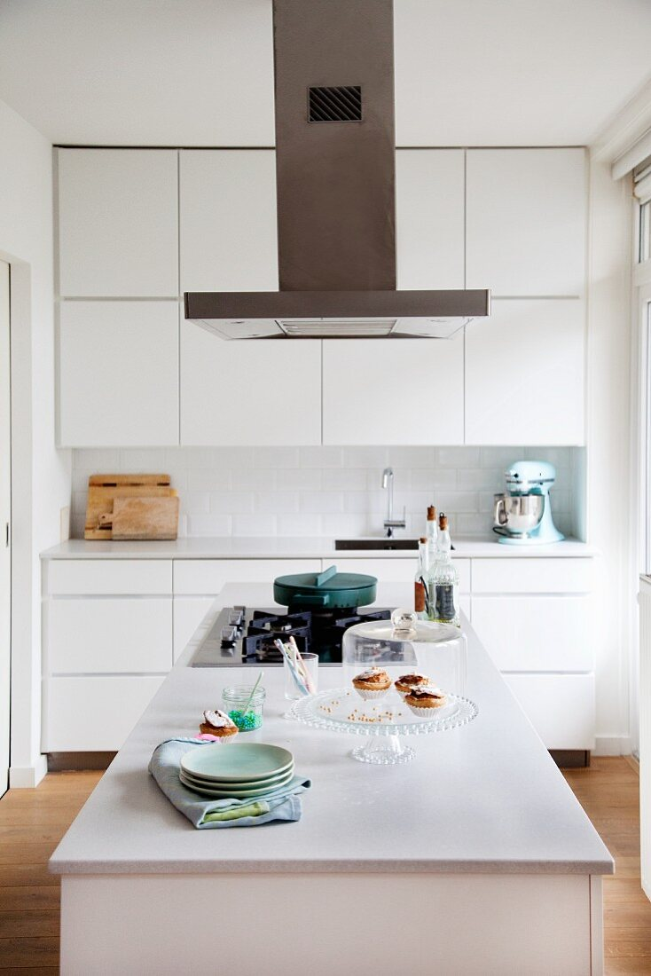 White fitted kitchen with wall units, extractor hood and island counter