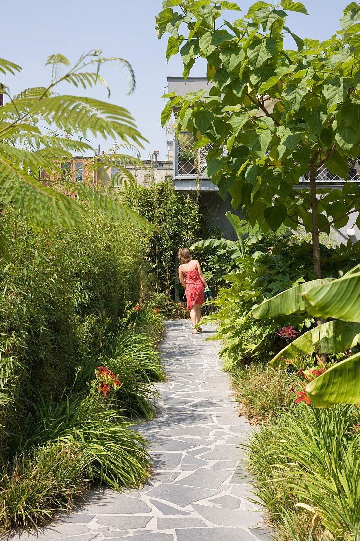 Woman walking along stone-flagged path leading through summery garden