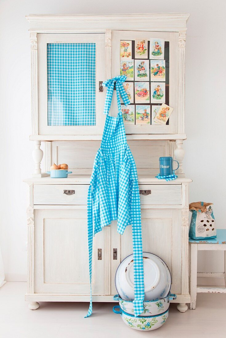 Blue and white checked apron hung from old kitchen dresser