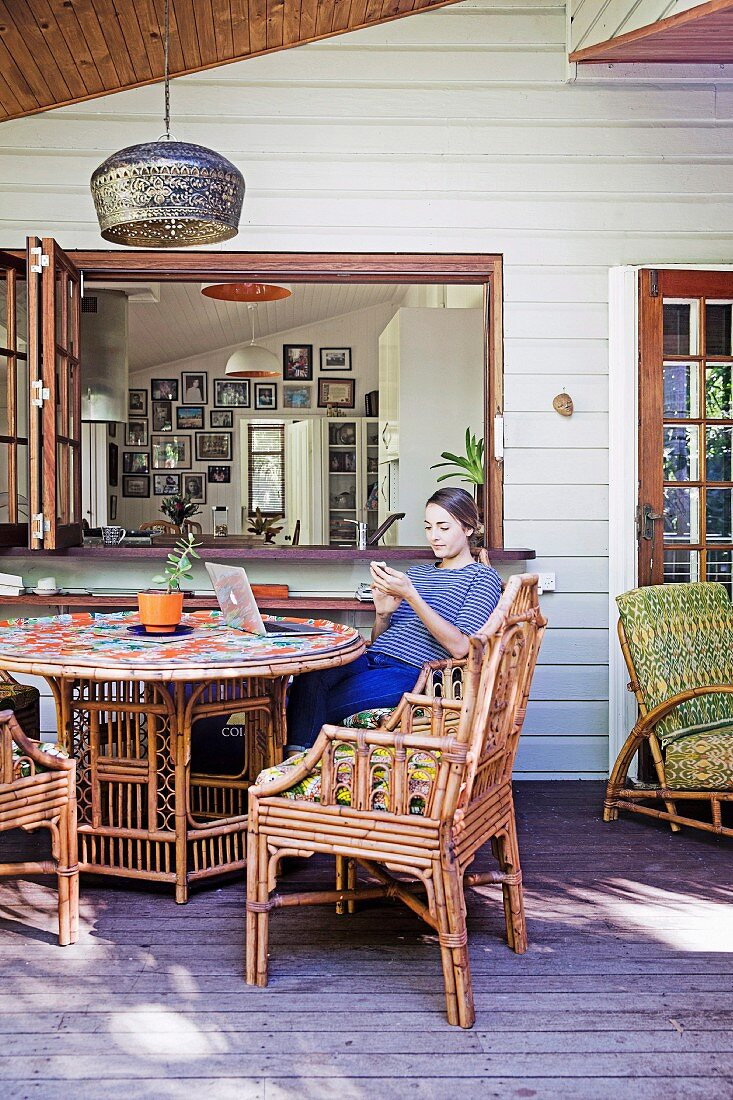 Young woman sitting on the porch with rattan furniture in front of the window