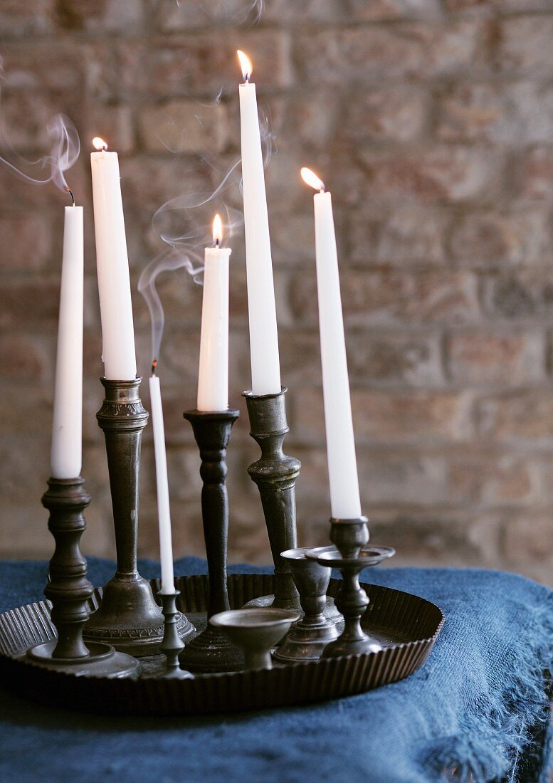 Collection of pewter candlesticks in old baking tray