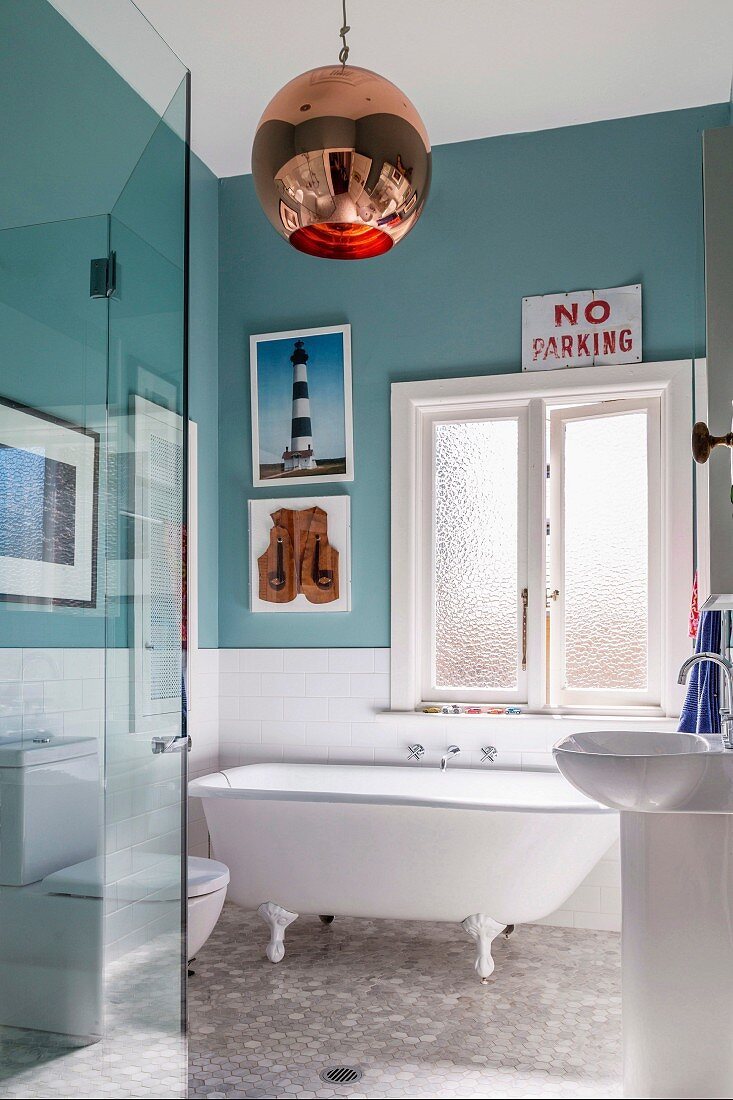 Bathroom with nostalgic freestanding bathtub, turquoise green wall paint and retro ball lamp;eclectic flair