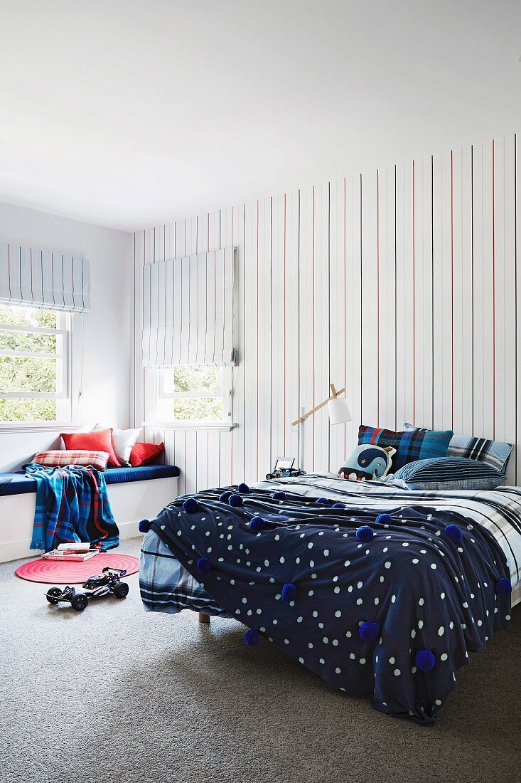 Bed and bench in the boy's room with a pattern mix