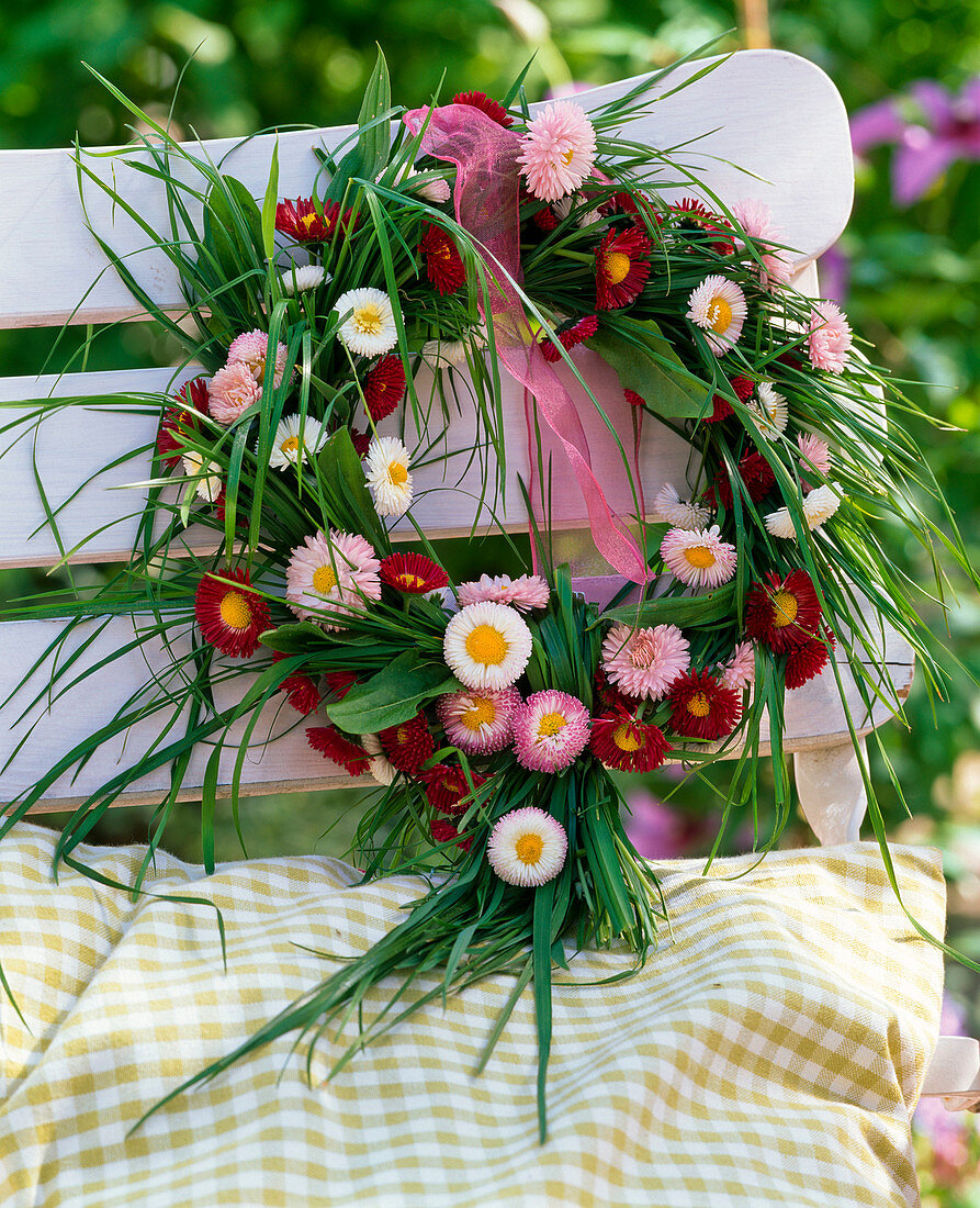 Bellis (daisies) and grasses wreath on the back of the chair
