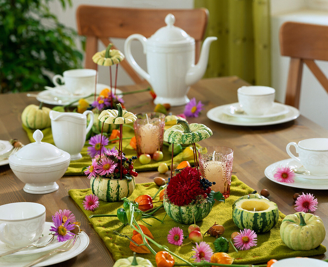 Table decoration with ornamental gourds as tealights and vases, aster flowers,