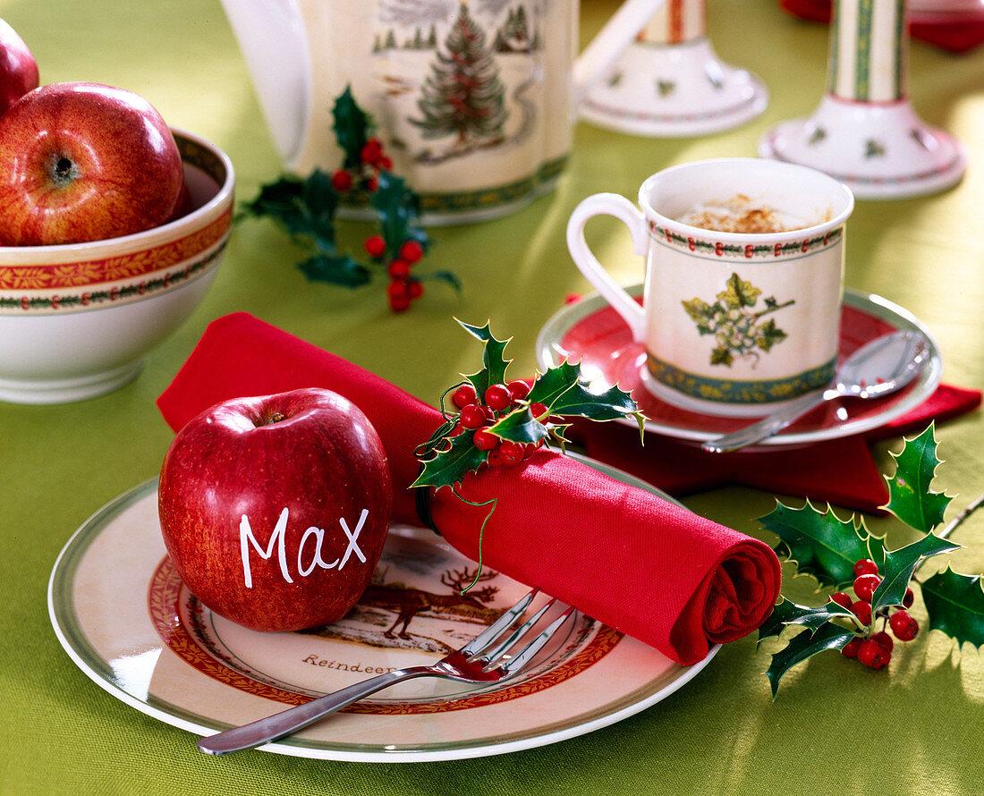 Ilex 'Alaska' / Stechpalme, Malus / Äpfel, rote Serviette, Weihnachtsgeschirr.