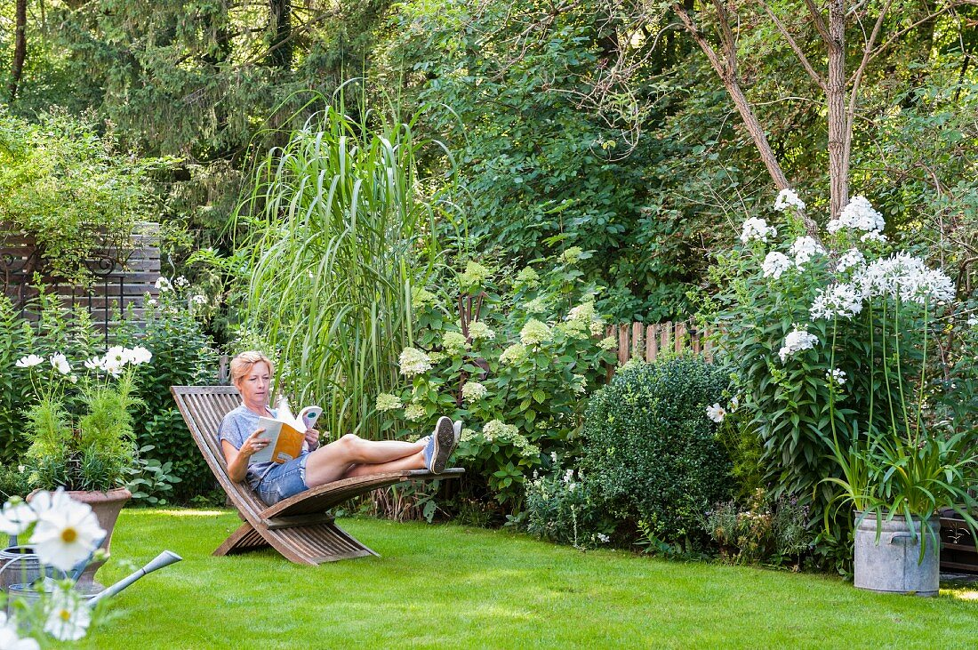 Woman reading on wooden lounger in … – Buy image – 12236497 ❘ living4media