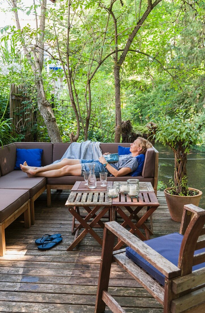 Woman relaxing on outdoor couch on secluded terrace next to stream