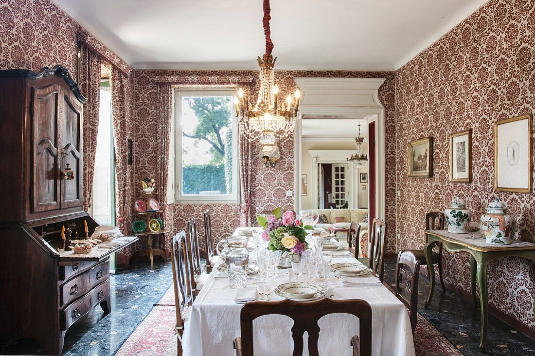 Festively set dining table in dining room with ornate wallpaper