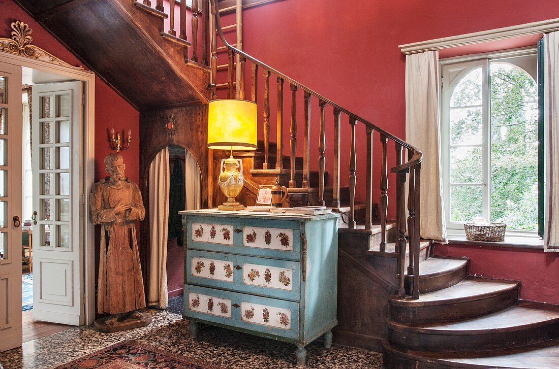 Lamp on old chest of drawers and statue of saint below old wooden staircase