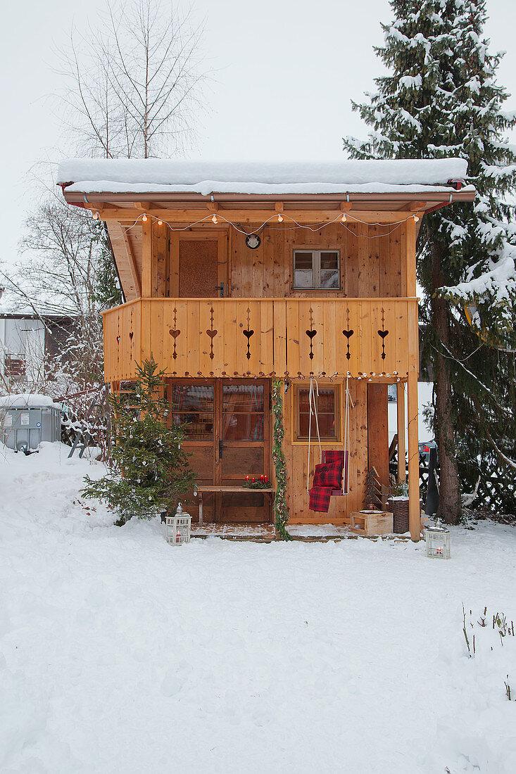 Alpine-style wooden cabin in snowy garden
