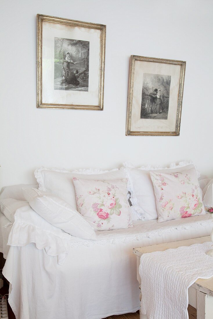 Vintage-style cushions on white loose-covered sofa below framed black and white photos