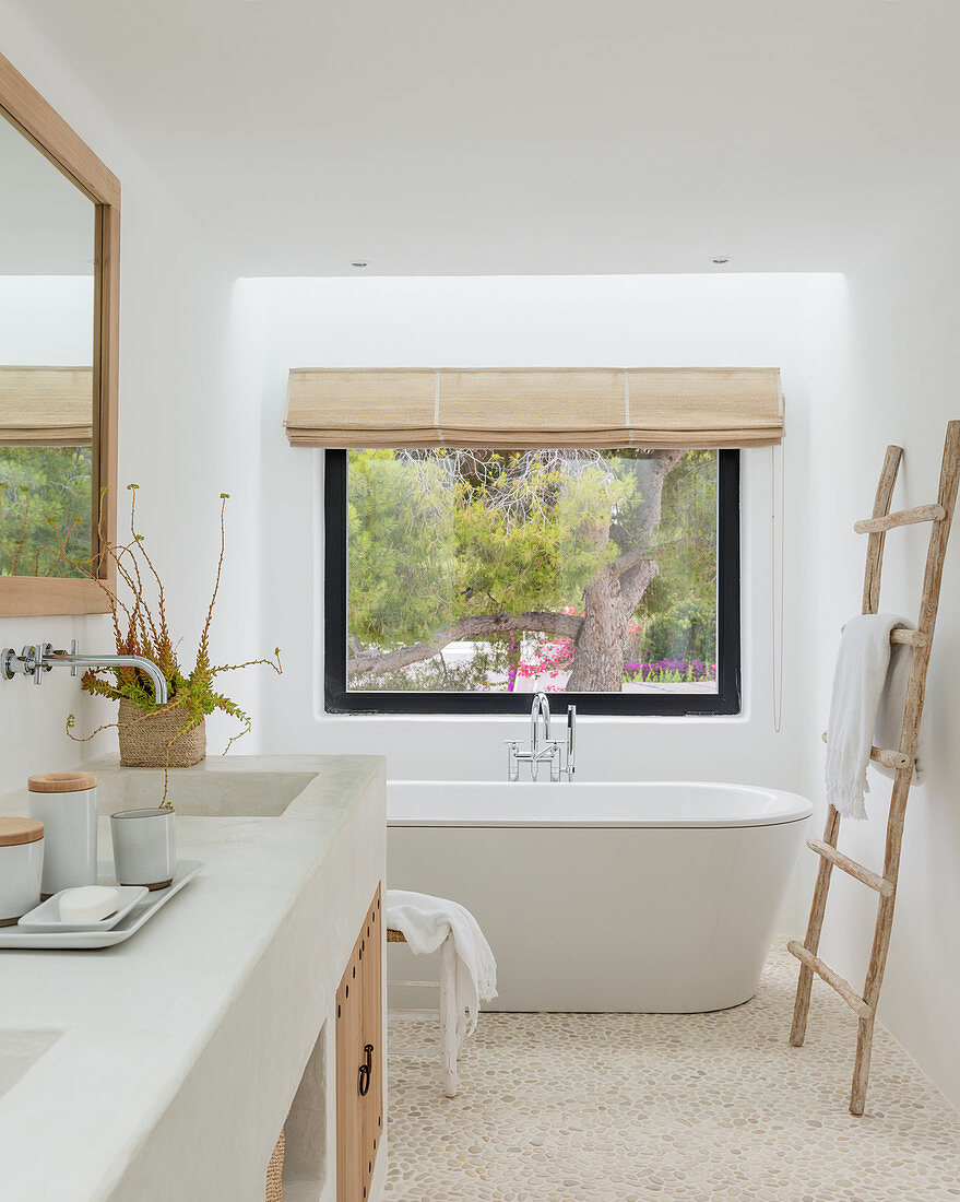 Free-standing bathtub under window in natural bathroom