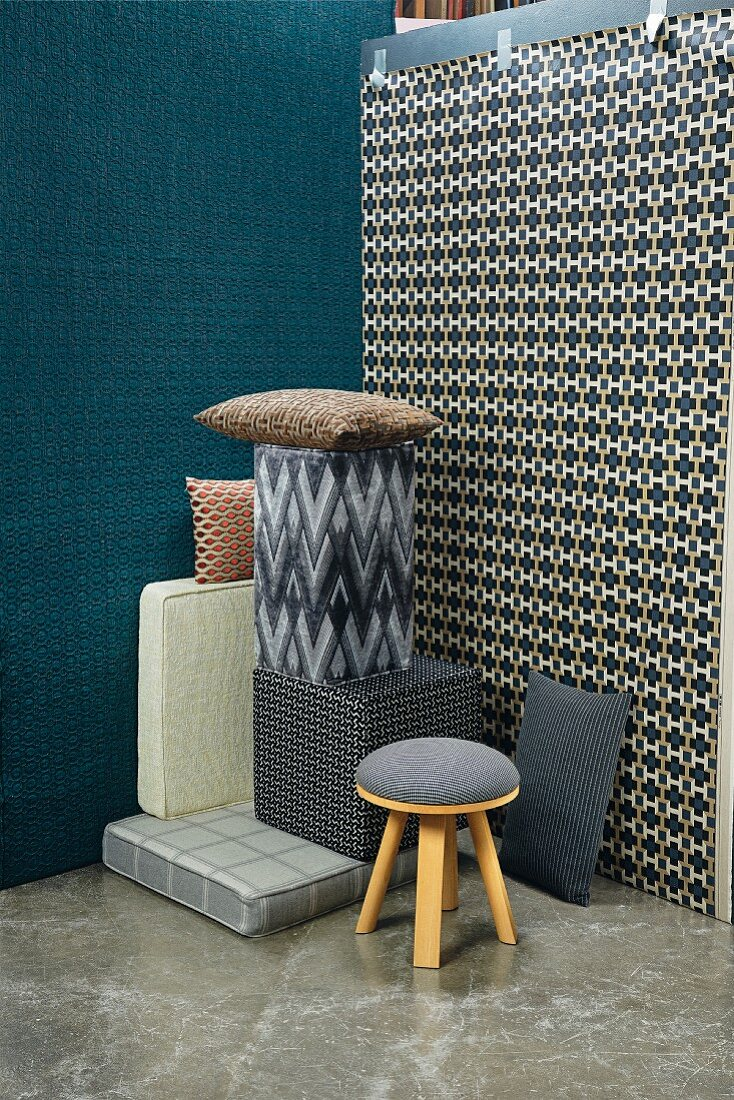 A pile of cushions, a stool and seating blocks in front of two walls with patterned wallpapers