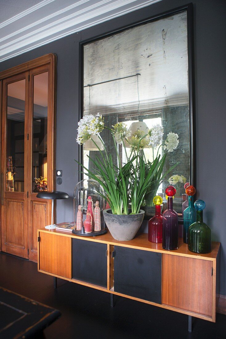 Colourful glass bottles and bowl of white-flowering plants on retro sideboard below mirror on wall
