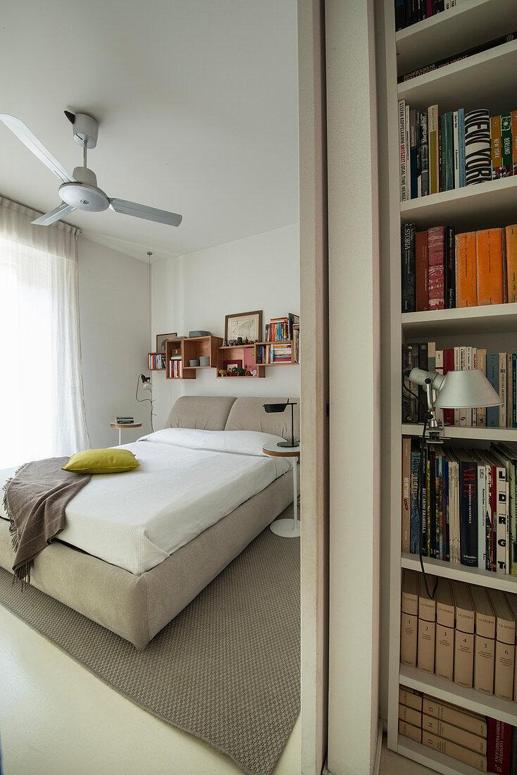 View into beige bedroom past bookcase