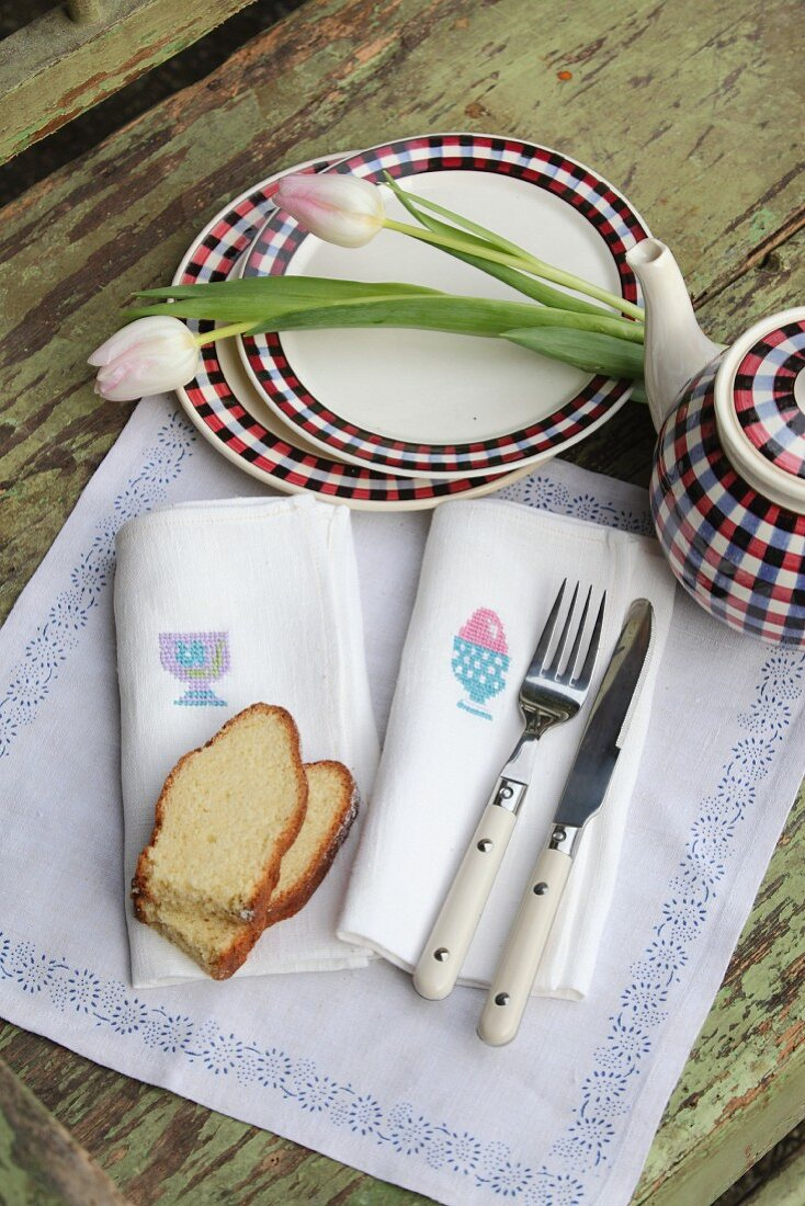 Napkin with cross-stitched Easter motifs, cake, cutlery, teapot, plates and tulips