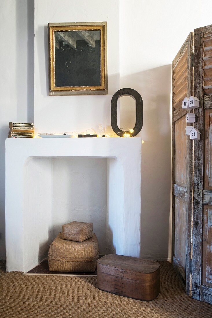 Stillgelegter weißer Kamin neben Vintage Paravent in renoviertem Landhaus