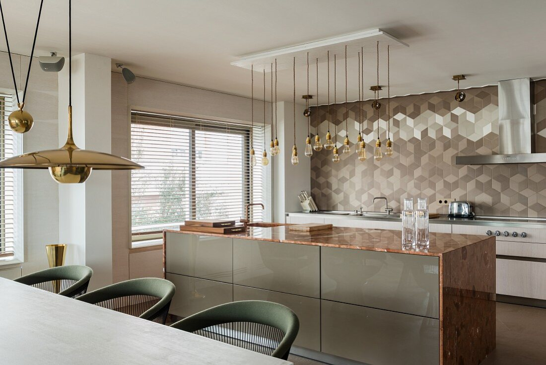 Kitchen island with marble worktop and geometric wall tiles in elegant, open-plan kitchen